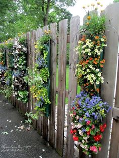 hanging planting bags filled with annuals  on garden fence.- hide the front yard fence