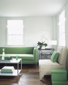 Green accents stand out in this white living room.