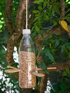 Quer fazer um comedouro? Pegue uma garrafa PET vazia e faça quatro pequenas aberturas, atravessando-as em X. Depois, é só inserir duas colheres de madeira na diagonal. Encha o recipiente com alpiste, e voilà!