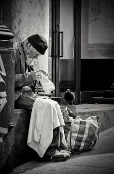 'Weaving the Life'  Beggar knitting sweaters for a cold winter approaching, with the single   pigeon as company