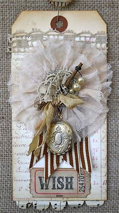 I adore the inclusion of a locket on this wonderfully dimensional tag. #vintage #shabby #chic #locket #lace #rosette #tag #handmade #crafts #paper #scrapbooking