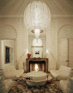 Lenny Kravitz Paris apt living room white glam fur chandelier 1970s chairs brass table fireplace tusks