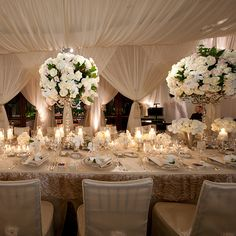 Luxurious reception décor. Love the elegant draping and the beautiful tall centerpieces