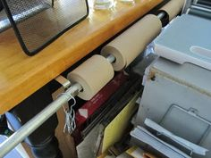 Curtain rod attached to sturdy table to hold roll goods like kraft paper, bubble wrap, whatever