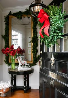 I love everything about this photo...the black door with boxwood wreath, the light fixture, the RED amaryllis arrangement, and the silver punchbowl filled with gifts!