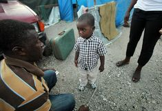 Haiti one year later: Beaudin Lovinsky, a 4-year-old orphan, is dropped off with his belongings in a suitcase by his uncle (left) to be placed in the Children's Foundation of Haiti orphanage, which is currently housed in makeshift tents in a tent city near the airport on January 10, 2011 in Port-au-Prince, Haiti. Lovinsky's mother perished in the earthquake and his uncle said he could no longer afford to take care of him. It is common for Haitian families to place children they cannot afford to care for in orphanages. The orphanage's building was damaged by the earthquake, forcing many of the orphans into tents. The orphanage has received no governmental assistance and little help from aid groups. According to the United Nations Children's Fund, Haiti was home to more than 350,000 orphans before the earthquake, with many more orphaned following the quake. UNICEF recently announced that around 380,000 Haitian children are still living in camps one year after the earthquake. (Mario Tama/Getty Images)