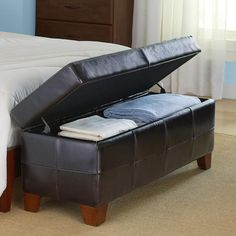 Bedroom storage bench is fully upholstered in elegant leather.