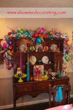 #ChristmasGarland #ColorfulChristmas Bright and beautiful ribbon, colorful ornaments and pops of black and white decorate this china cabinet.