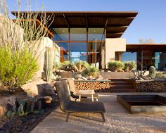 A pivot door opens from a living room to the cacti-planted patio leading down to a fire pit at the Brown residence in Scottsdale, Arizona, designed by Lake | Flato Architects.