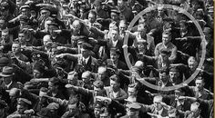 A German man, August Landmesser, standing at a rally in 1936 Hamburg refuses to give the Nazi salute. It's a an now-iconic photo of civil disobedience.
