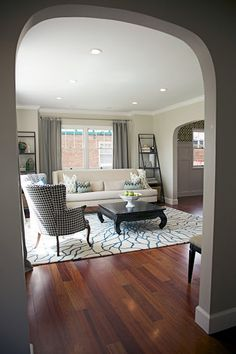 A lovely gray living room with cream sofa, wingback armchair and wood coffee table