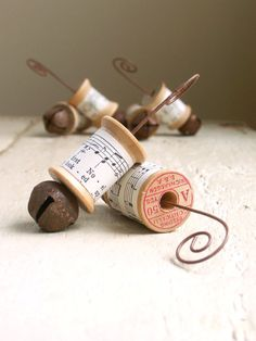 Adorable ornaments ~~ made from vintage wood thread spools.    Inspiring Hymns sheet music from the 1950s wraps around each spool, a rusty jingle bell