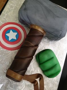 Avengers Assemble! Edible Captain America's shield and Hulk's hand, with Thor's hammer as the cake. By Cake Delight.
