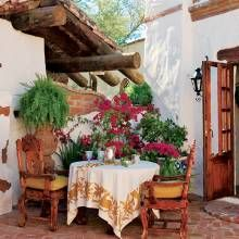 With delicate camellias, Mexican ferns and bright-pink bougainvilleas, this courtyard off the living room is an inviting place to enjoy morning coffee. Within view of the table is a sampling of the home's authentic Mexican-style architectural details, including an overhang with wood beams and vigas, a tile roof, brick that peeks through the stucco on the courtyard wall, and sculptural relief work.