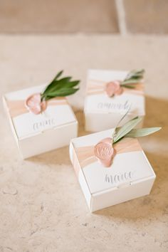 wedding favors that also served as wedding placecards grey watercolor calligraphy on luxe white boxes || blush silk ribbon, blush wax seal and fresh olive for a wedding on lake como calligraphy || @dellatorredesigns photography || @mikelarson