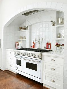 range in arched niche with open shelving, white Viking range