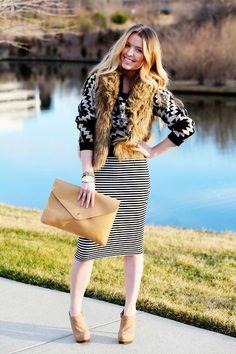 Patterned sweater, faux fur vest, striped skirt + oversized clutch.