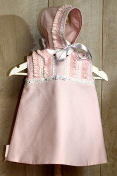 Sofisticado vestido de bebé niña confeccionado en piqué rosa con adornos en blanco realizados artesanalmente
