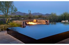 A sleek, contemporary pool and firepit bordered by   luxurious seating offer a dramatic vantage beneath Arizona mountains. The REIN Model by K. Hovnanian  Homes. Scottsdale, AZ.