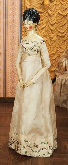 Doll, ca 1800wearing early silk dress with crewel embroidery detail,and owning an additional green silk coat with matching bonnet designed to accommodate the voluptuous coiffure.