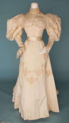 1895 silk and lace wedding gown. Two-piece white ribbed silk, pearl studded high collar, trained skirt and fringed sash with leg-'o-mutton sleeves.