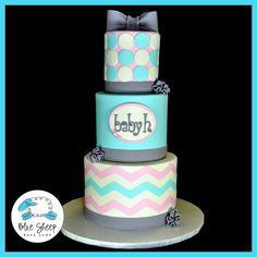 Three tiered pink, blue, white, and grey baby shower cake with chevrons and geometric circle pattern.