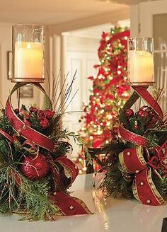 Create a cheerful holiday display in your home this Christmas with the Set of Two Glad Tidings Candle Holders that features festive ribbon, lifelike greenery and embellishments like berries, ornaments and gold bells.