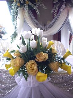 Yellow roses, yellow calla lilies and white tulips.