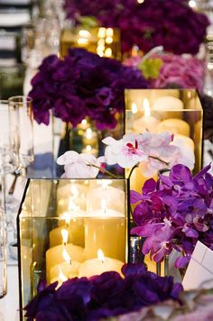 Tinted shadow boxes are filled with a trio of pillar candles and surrounded by fresh purple and white orchids.