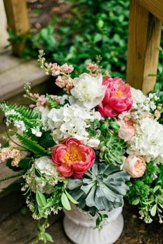 Lush arrangement of peonies, roses, succulents, hydrangeas, ferns, and other blooms