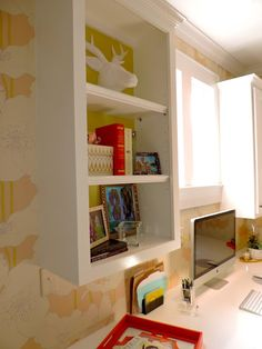 We pulled bright books and accessories from HomeGoods to layer the shelves in this home office. The painted background is a simple way for the shelves to pop!