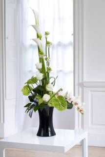 Spirits - A modern linear display, overflowing with exotic flowers and foliages - arranged in this classic black glass container.