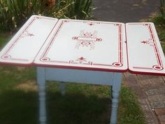 enamel top tables....1930's - 1950  Gramma had one . We had one that  was our kitchen table. It was outlined in red without the fancy design. The legs were metal, not blue wood.