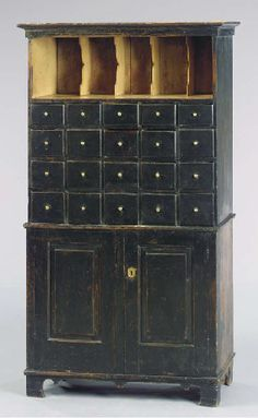 A BLACK-PAINTED APOTHECARY CABINET   AMERICAN, EARLY 19TH CENTURY   70½in (178cm.) high, 40in. (102cm.) wide, 15½in. (39cm.) deep