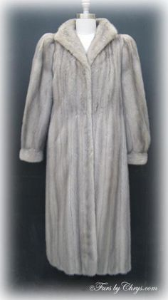 Silver Mink Coat #SM728; Very Good Condition; Misses 8 - 12. This is a beautiful genuine natural silver mink fur coat. It has a Dion Furs label as well as an EMBA American Mink label (very high quality pelts), and features a wing-style collar and banded bracelet cuffs. The lining is solid silver-grey with stunning floral embroidery at the bottom edge. You would look lovely wearing this glamorous silver mink coat anywhere that calls for a touch of sophistication. You will feel regal!