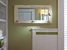 Add glass and brass hooks to an old window for a rustic chic bathroom mirror.
