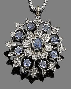 A sapphire and diamond floral brooch/pendant.  The openwork plaque set to the centre with an oval-cut sapphire, within a surround of cushion-shaped and single-cut diamonds, to further rows of circular-cut sapphires and single and rose-cut diamonds, to a later 18 carat white gold venetian-link chain, diamonds approx. 0.30ct total, chain with partial UK hallmark, lengths: pendant 3.5cm, chain 45.5cm