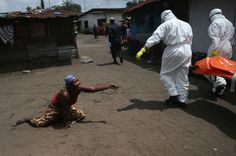 A woman throws a handful of soil toward the body of her sister, a twenty-eight-year-old market vender who collapsed outside her home on the morning of October 10, 2014, as it is removed for cremation. The World Health Organization has projected that the number of new Ebola infections in the countries worst affected by the virus—Guinea, Liberia, and Sierra Leone—could increase from 1,000 per week to 10,000: http://nyr.kr/1oaB8oM (Photograph by John Moore / Getty)