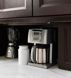 Motorized doors slide closed to conceal kitchen clutter, like coffee pots and other appliances - Traditional Home®
