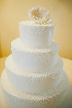 Traditional white wedding cake with a sugar peony on top.