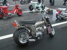 Honda Cub custom with bare metal frame, large rear tire and custom exhaust