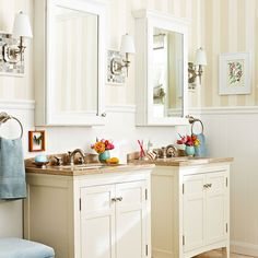 Bathroom with tiled wall sconces over wood vanities