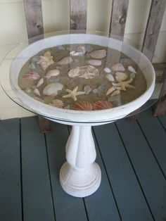 BIRDBATH FILLED WITH SAND AND SEASHELLS COVERED WITH A GLASS TOP MAKES A CUTE SUNROOM TABLE