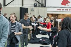 Passing out free T-shirts to the first 500 students that arrived at #TeamUCM night at the Blackout Game.