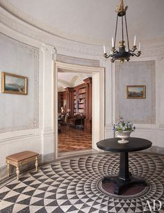 Paved with a Roman-inspired mosaic, the elliptical entrance hall of a Naples, Italy, apartment designed by Studio Peregalli features a French Empire chandelier and an antique English lavastone pedestal table.