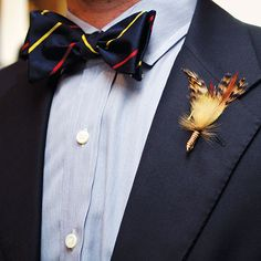 Nick donned a Polo Ralph Lauren suit, a Ben Silver bow tie, and a boutonniere he tied himself from fly-fishing materials. (IN Photography) AWESOME