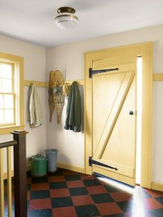 A barn-style door and a pine floor painted to mimic old linoleum add character to this farmhouse mudroom. | Photo: Tria Giovan | thisoldhouse.com