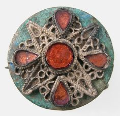 Disk Brooch, Frankish or northern French, 550-600 CE.  Copper alloy, silver wire and glass paste.  Dimensions: Overall: 1 3/16 x 7/16 in. (3 x 1.1 cm) Classification: Metalwork-Copper alloy. Credit Line: Gift of J. Pierpont Morgan, 1917. Accession Number: 17.192.81.  In the Metropolitan Museum of Art, New York.