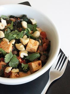 Healthy Indian Tofu Curry | POPSUGAR Fitness 1 large bunch of red Swiss chard or rainbow chard (around 16 to 18 leaves) 3 tablespoons olive oil 1 onion, chopped 1 tablespoon ginger, minced 3 cloves garlic, minced 1 teaspoon turmeric 1 teaspoon garam masala 1/2 teaspoon red chili flakes 1 teaspoon cumin powder 1 teaspoon kosher salt 1 tomato, chopped 1 block extrafirm tofu, cubed 1 cup water 1/4 cup roasted cashews, for garnish 1/4 cup chopped cilantro, for garnish