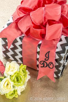"""Here's a fun and fast idea: Put a custom touch on a basic wrapping job by adding iron-ons to wire-edged fabric ribbon. We say """"I do!"""" to this custom idea."""